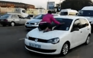 Scorned woman clings to windscreen of cheating husband's car