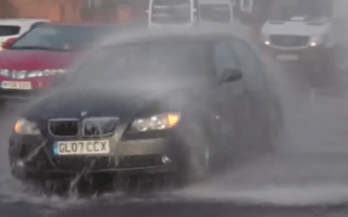 BMW driver uses burst water main as free car wash