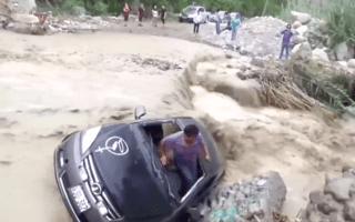 Video shows man's dramatic escape as car is washed away