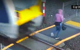 Jaw-dropping moment woman nearly hit by train on level crossing