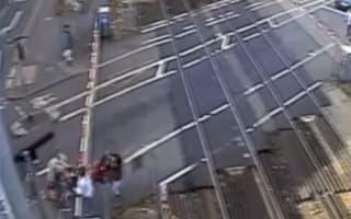 Shocking moment women lift children and pram over level crossing