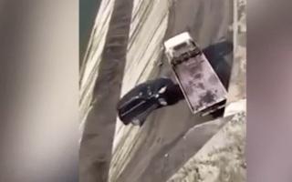 Breakdown vehicle pushes stricken car off ledge