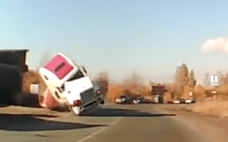 Dashcam captures moment truck tips over on busy road