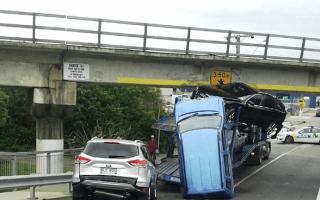 Car transporter gets wedged under bridge