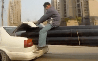 Man caught riding massive pipes sticking out of a moving car