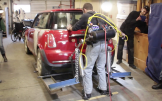 Man wearing exoskeleton defies belief to lift Mini Cooper