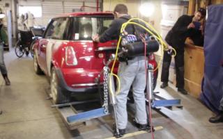 Man wearing exoskeleton defies belief to lift Mini Cooper