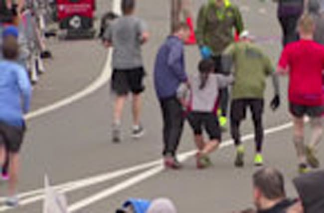 Exhausted runner helped across finish line by competitors
