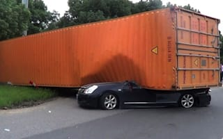 Woman walks away after car is flattened by shipping container