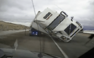 Lorry blows over onto police car