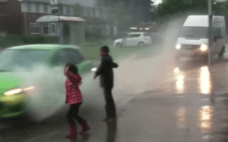 Mum criticised after letting kids get splashed by passing cars