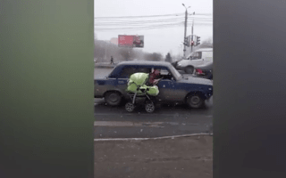 Motorists caught pulling a pram alongside a car on busy road