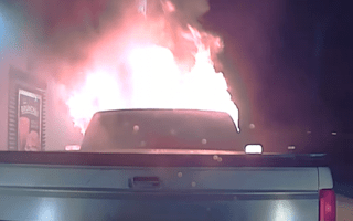 Police cruiser pushes burning truck away from restaurant
