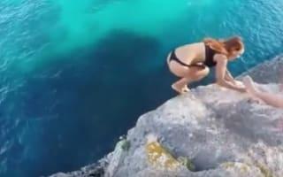 Girl grabs for boyfriend's leg in failed cliff dive, he pulls away