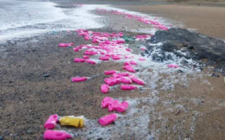 Thousands of pink bottles wash up on beach in Cornwall