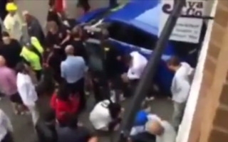 Passers-by help lift car off trapped cyclist