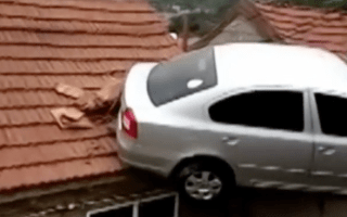 Car gets stuck on a house roof after crashing through brick wall