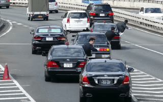 The Japanese Prime Minister merges with traffic aided by men in white gloves