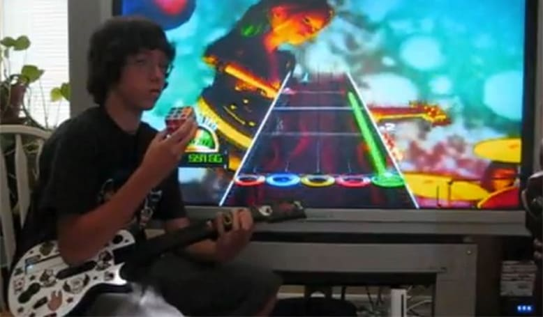 Kid plays Guitar Hero while solving two Rubik's Cubes