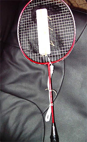 A Wii remote strapped onto a badminton racket