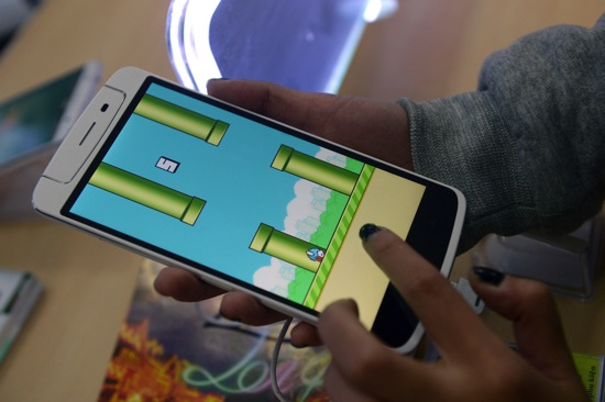 An employee plays the game Flappy Bird at a smartphone store in Hanoi on February 10, 2014.  The Vietnamese developer behind the smash-hit free game Flappy Bird has pulled his creation from online stores after announcing that its runaway success had ruined his
