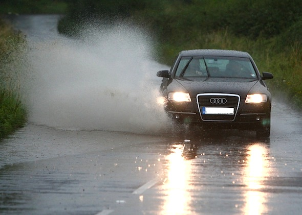 A car goes through a puddle near Fernham, Oxfordshire, as wet weather continues across the UK.