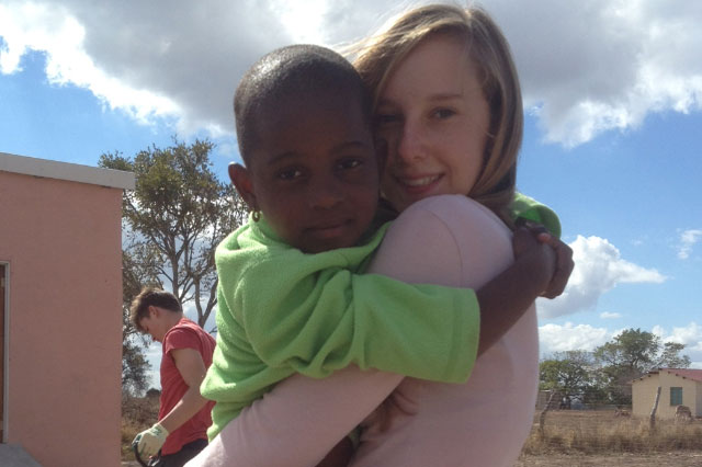 Emily cuddles a nine-year-old orphaned African girl in Bush Buck Ridge