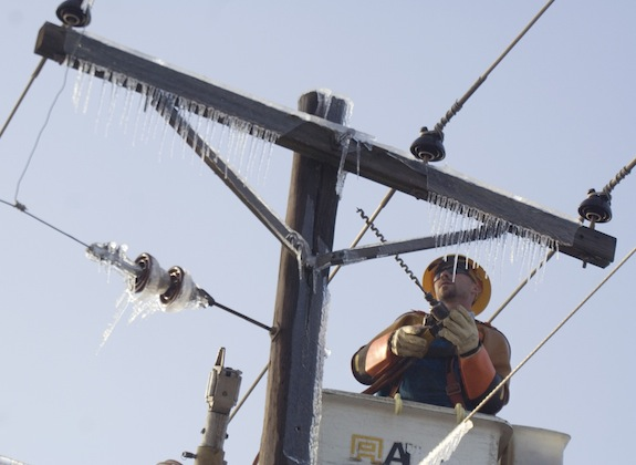 Michael Proske with Pike Electric, Inc. out of San Marcos, Texas, works to secure a telephone pole in Springdale, Ark. on Thursday, Jan. 29, 2009. Thousands in the city are without electricity following an ice storm that hit the northwest Arkansas region on Tuesday. (AP Photo/Beth Hall)