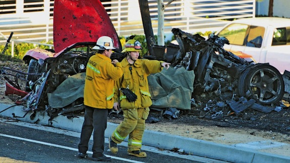 Sheriff's deputies work near the wreckage of a Porsche that crashed into a light pole on Hercules Street near Kelly Johnson Parkway in Valencia, Calif., on Saturday, Nov. 30, 2013. A publicist for actor Paul Walker says the star of the