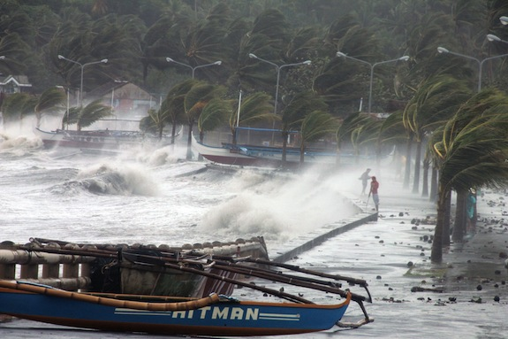 Residents (R) stand along a sea wall as high waves pounded them amidst strong winds as Typhoon Haiyan hit the city of Legaspi, Albay province, south of Manila on November 8, 2013.  One of the most intense typhoons on record whipped the Philippines on November 8, killing three people and terrifying millions as monster winds tore roofs off buildings and giant waves washed away flimsy homes.AFP PHOTO/CHARISM SAYAT        (Photo credit should read Charism SAYAT/AFP/Getty Images)