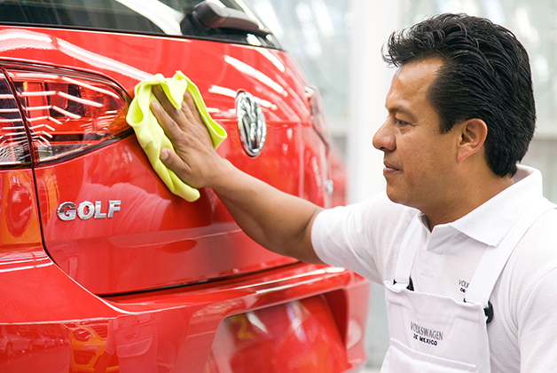 A factory worker polishes a Volkswagen Golf in Puebla, Mexico
