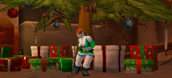 A female dwarf in a green santa suit, posing under a christmas tree in Ironforge
