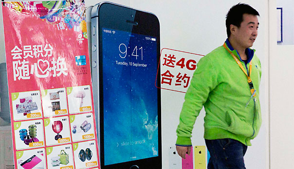 A man walks in front of a China Telecom advertisement for the iPhone with the Chinese characters