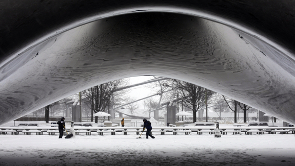 A park crew clears the snow around Annish Kapoor's stainless steel Cloud Gate sculpture at Millennium Park, Thursday, Jan. 2, 2014, as snow continues to accumulate in downtown Chicago. More snow could fall across the Chicago metro area Thursday, according to the National Weather Service. (AP Photo/Kiichiro Sato)