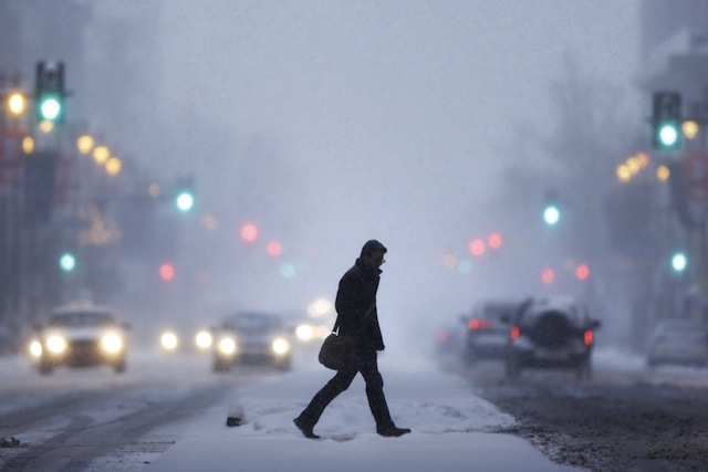 A man crosses Broad Street during a winter snowstorm Tuesday, Jan. 21, 2014, in Philadelphia. A swirling storm with the potential for more than a foot of snow clobbered the mid-Atlantic and the urban Northeast on Tuesday, grounding thousands of flights, closing government offices in the nation's capital and making a mess of the evening commute. (AP Photo/Matt Rourke)