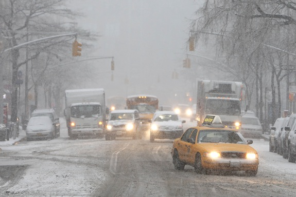Traffic makes its way slowly down Hudson Street as heavy snow falls Monday, Feb. 3, 2014, in New York. After several days of mild weather, snow has returned to the Northeast. (AP Photo/Jason DeCrow)