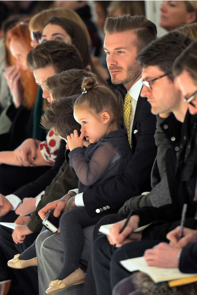 Soccer great David Beckham with his daughter Harper look on as models present the fashions of Victoria Beckham during the Mercedes-Benz Fashion Week Fall/Winter 2014 shows February 9, 2014 in New York City. AFP PHOTO / Don EMMERT        (Photo credit should read DON EMMERT/AFP/Getty Images)