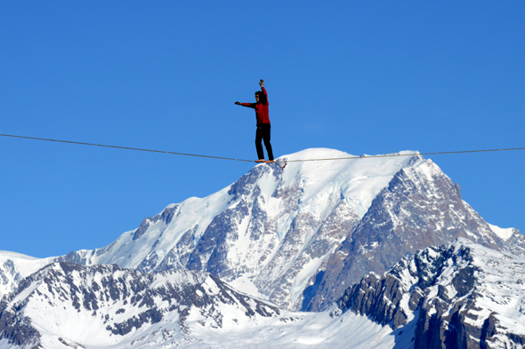 French highliner Julien Millot performs on the Paradiski cable way, 380m high, designed by French creator Jean-Charles de Castelbajac, on December 16, 2013 in front of the Mont Blanc mountain in La Plagne.      AFP PHOTO / JEAN-PIERRE CLATOT        (Photo credit should read JEAN-PIERRE CLATOT/AFP/Getty Images)