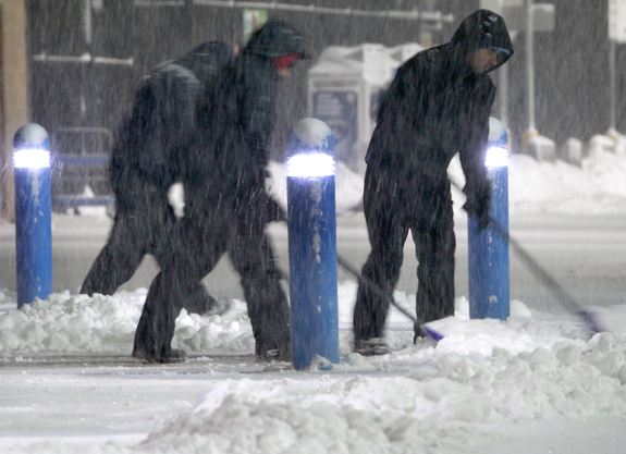 Workers clears snow from the sidewalk outside a business Saturday, Feb. 15, 2014, in the Boston suburb of Hudson, Mass. Another round of snow made its way into the Northeast on the heels of a storm that brought snow and ice to the East Coast, caused at least 25 deaths and left hundreds of thousands without power. (AP Photo/Bill Sikes)