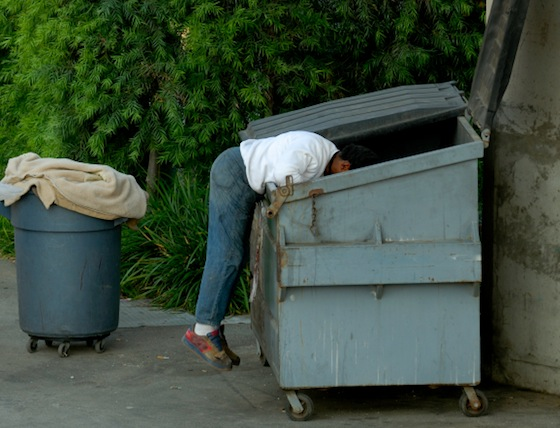 Homeless man digging through dumpster in Los Angeles California