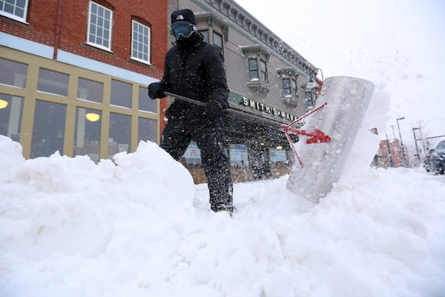 Earl Barnes shovels snow off the sidewalk in front of Smith's Market on S. Main St. in Hutchinson, Kan., Tuesday, Feb. 4, 2014. The winter storm dumped more than 10 inches of snow on the city from late Monday to late Tuesday. (AP Photo/The Hutchinson News, Travis Morisse)