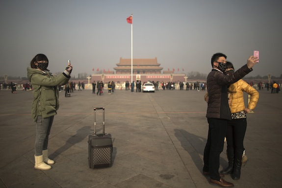 Tourists use mobile phones to take photos of themselves wearing masks on a heavily polluted day on Tiananmen Square in Beijing, China, Thursday, Jan. 16, 2014. Beijing's skyscrapers receded into a dense gray smog Thursday as the capital saw the season's first wave of extremely dangerous pollution, with the concentration of toxic small particles registering more than two dozen times the level considered safe. (AP Photo/Alexander F. Yuan)