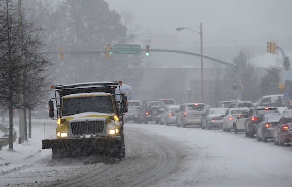 A truck using a snow-plow clears a street in Chapel Hill, N.C., Wednesday, Feb. 12, 2014. A major winter slammed into North Carolina Wednesday, turning homebound commutes that typically take minutes into hours-long ordeals as traffic slowed to a slippery slog and threatening to leave many areas dark because of power outages. (AP Photo/Gerry Broome)