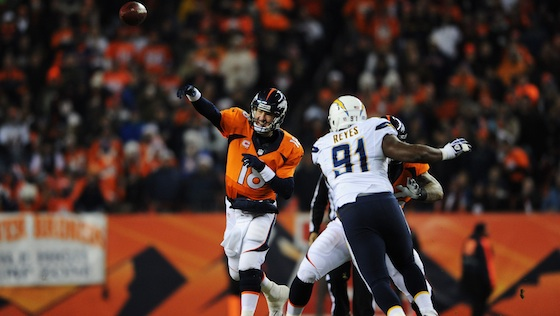 DENVER, CO - DECEMBER 12:   Peyton Manning #18 of the Denver Broncos thows a first quarter pass under pressure from Kendall Reyes #91 of the San Diego Chargers at Sports Authority Field at Mile High on December 12, 2013 in Denver, Colorado.  (Photo by Dustin Bradford/Getty Images)