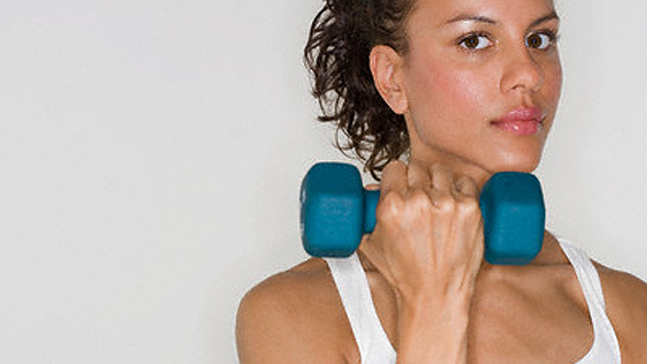 Young Woman Lifting Dumbbell --- Image by ? Royalty-Free/Corbis