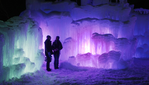 In this Wednesday, Jan. 8, 2014 photo, patrons tour an ice castle at the base of the Loon Mountain ski resort in Lincoln, N.H. The ice castle begins to grow in the fall when the weather gets below freezing and thousands of icicles are made and harvested then placed around sprinkler heads and sprayed with water.  The castle will continue to grow as long as the temperatures stay below freezing. (AP Photo/Jim Cole)
