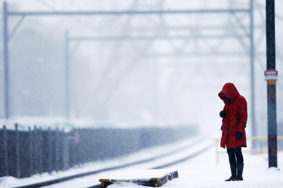 A morning commuter waits on a train during a winter snowstorm Monday, March 3, 2014, in Philadelphia. (AP Photo/Matt Rourke)