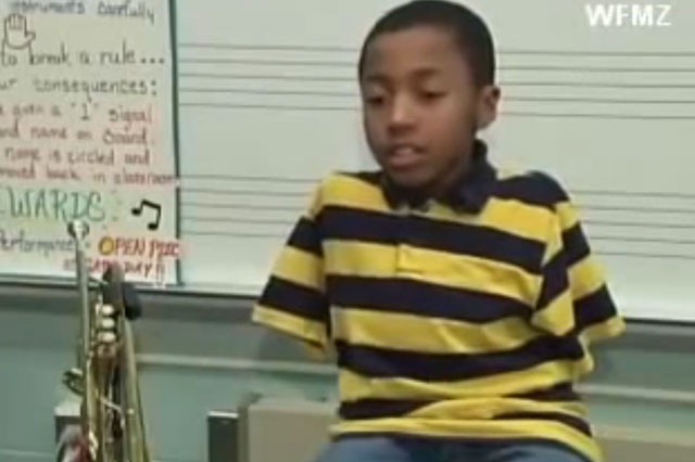 Boy plays trumpet with his toes