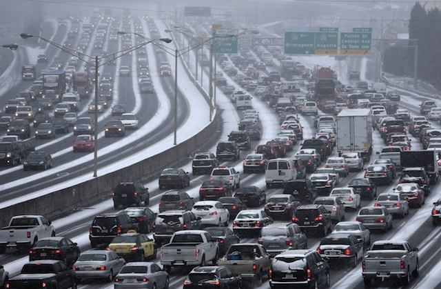 Traffic inches along the connector of Interstate's 75 and 85 as snow blankets Metro Atlanta on Tuesday afternoon, Jan. 28, 2014 as seen from the Pryor Street overpass.  Georgia Gov. Nathan Deal is preparing to declare a state of emergency as a winter storm coats the region with snow and ice. State transportation officials said a mass of commuters leaving downtown Atlanta at once created traffic jams on interstates and surface streets. (AP Photo/The Atlanta Journal-Constitution, Ben Gray)