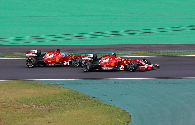 Ferrari drivers Kimi Raikkonen and Fernando Alonso race at the 2014 Brazilian F1 Grand Prix.